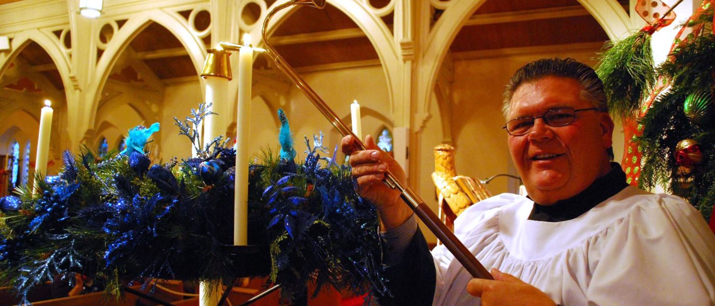 man lighting candles on Advent wreath
