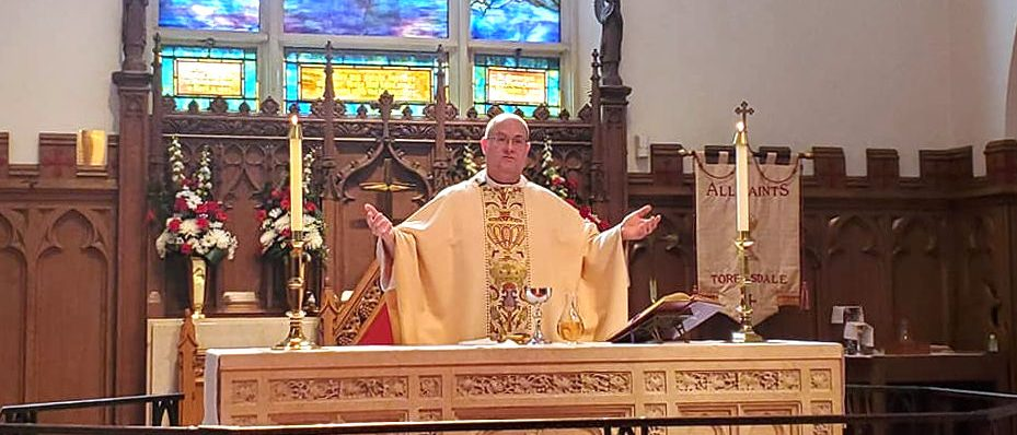 priest with arms outstretched standing behind altar